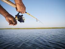 Mains retenant le pôle de pêche. image libre de droits
