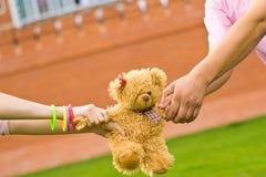 Mains retenant le petit ours de nounours Photographie stock libre de droits