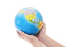 Mains retenant le puzzle denteux de globe Images libres de droits