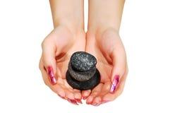 Mains retenant les roches volcaniques Images stock
