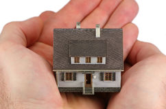 Mains retenant une maison miniature Photos stock