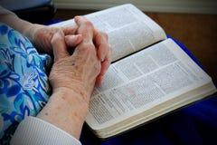 Mains saintes Gnarly sur la bible photos stock