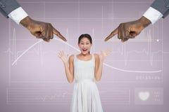 Mains se dirigeant à la femme étonnée d'affaires sur le fond rose avec l'électrocardiogramme Photos stock