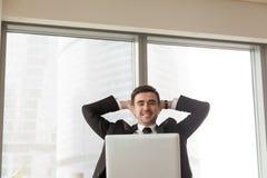 Mains se reposantes d'homme d'affaires heureux décontracté derrière la tête regardant l photo stock