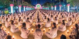 Mains se reposantes de panorama bouddhiste dans la prière dans illuminé par des bougies Photos stock