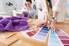 Mains sensibles d'un tailleur sur la table de fonctionnement Image stock