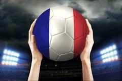 Mains soulevant un ballon de football Photo libre de droits