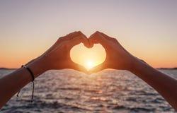 Mains sous forme de coeur au coucher du soleil et dans la perspective de la mer Photo stock