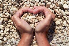 Mains sous forme de coeur avec des cailloux à l'intérieur Photo stock