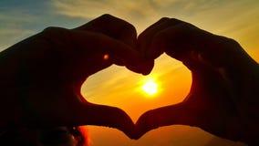 Mains sous forme de coeur contre le lever de soleil d'or dramatique Photos libres de droits