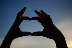 Mains sous forme de coeur contre le soleil et le ciel d'un lever de soleil ou d'un coucher du soleil Amour, bonheur, sentiments Images stock