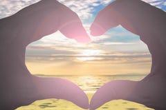 Mains sous forme de coeur sur la plage brouillée et le beau ciel Image libre de droits