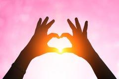 Mains sous une silhouette en forme de coeur Fond brouillé de Val Photos libres de droits