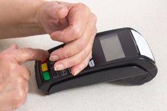 Mains supérieures de bâche de femme tout en introduisant le numéro d'identification personnelle sur le terminal de paiement image stock