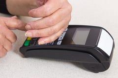 Mains supérieures de bâche de femme tout en introduisant le numéro d'identification personnelle sur le terminal de paiement images stock