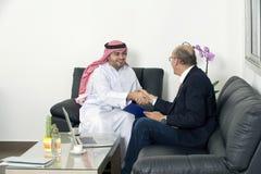 Mains supérieures de Shaking d'homme d'affaires avec l'homme d'affaires Arabe Photographie stock