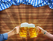 Mains supportant des tasses de bière sous le drapeau bavarois Photographie stock libre de droits