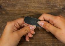 Mains sur la table avec la manucure Le sawing fait la forme du clou Image stock