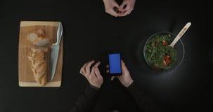Mains sur la table de cuisine Mains mettant en rouleau l'écran de téléphone Vue supérieure banque de vidéos