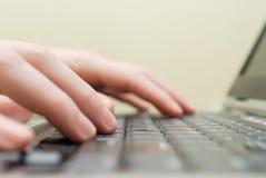 Mains sur le plan rapproché d'ordinateur portatif Photographie stock libre de droits