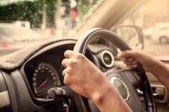 Mains sur le volant de la conduite Images libres de droits