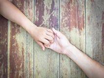 Mains sur un conseil en bois Images stock