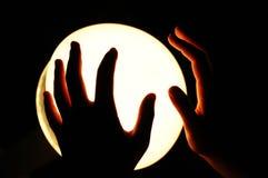 Mains sur un globe rougeoyant Photos stock