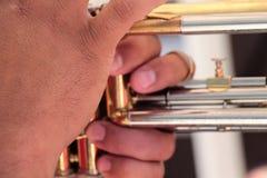 Mains sur un instrument en laiton, jouer de musiciens extérieur, fin  images libres de droits