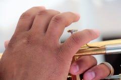 Mains sur un instrument en laiton, jouer de musiciens extérieur, fin  photo libre de droits