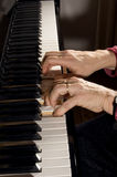 Mains sur un piano Photographie stock
