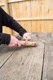Mains taillant la branche au couteau Photos stock