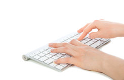 Mains tapant sur le clavier d'ordinateur sans fil lointain photographie stock
