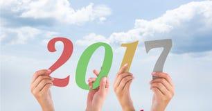 Mains tenant 2017 contre une image composée 3D de ciel Images stock