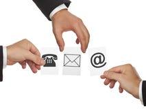 Mains tenant des cartes avec des symboles de téléphone, de courrier et de lettre - commun Photos stock