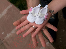 Mains tenant des chaussures de bébé Attente de la chéri Grossesse Photos stock