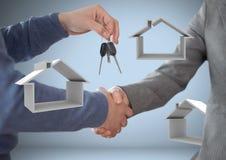 Mains tenant des clés avec des icônes de maison devant la vignette avec la poignée de main Image stock