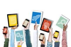 Mains tenant des dispositifs de Digital avec de divers symboles photographie stock