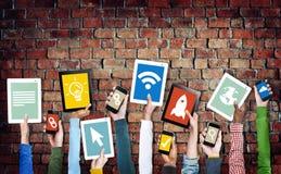 Mains tenant des dispositifs de Digital avec de divers symboles images libres de droits