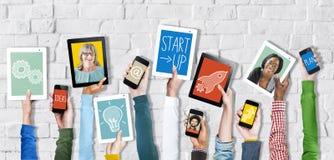 Mains tenant des dispositifs de Digital avec des concepts de démarrage image libre de droits