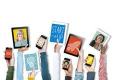 Mains tenant des dispositifs de Digital avec des photos image stock