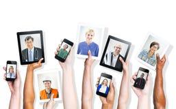 Mains tenant des dispositifs de Digital avec les images des personnes professionnelles photographie stock libre de droits