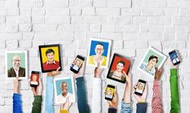 Mains tenant des dispositifs de Digital avec les visages des personnes Photographie stock