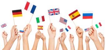 Mains tenant des drapeaux des Etats Membres des Etats-Unis et d'UE Images stock