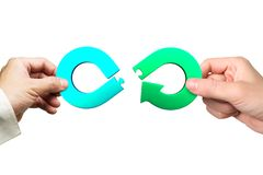 Mains tenant des morceaux de puzzle denteux d'infini de flèche, concept circulaire d'économie photos stock
