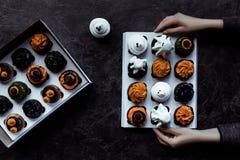 Mains tenant des petits gâteaux de Halloween Images libres de droits