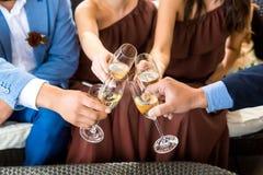 Mains tenant des verres et grillant, moment de fête heureux, concept de luxe de célébration Photos stock