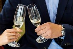 Mains tenant des verres et grillant, moment de fête heureux, concept de luxe de célébration Image libre de droits