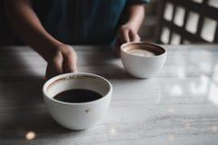 Mains tenant deux tasses blanches de café chaud sur la table en café Image stock
