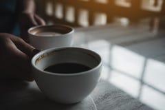 Mains tenant deux tasses blanches de café chaud sur la table en café Photos stock