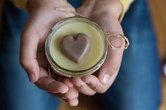 Mains tenant la crème corporelle avec le coeur en dedans Photographie stock libre de droits